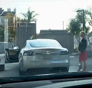 Elektrikli Tesla aracına benzin doldurmaya çalışan kadın.