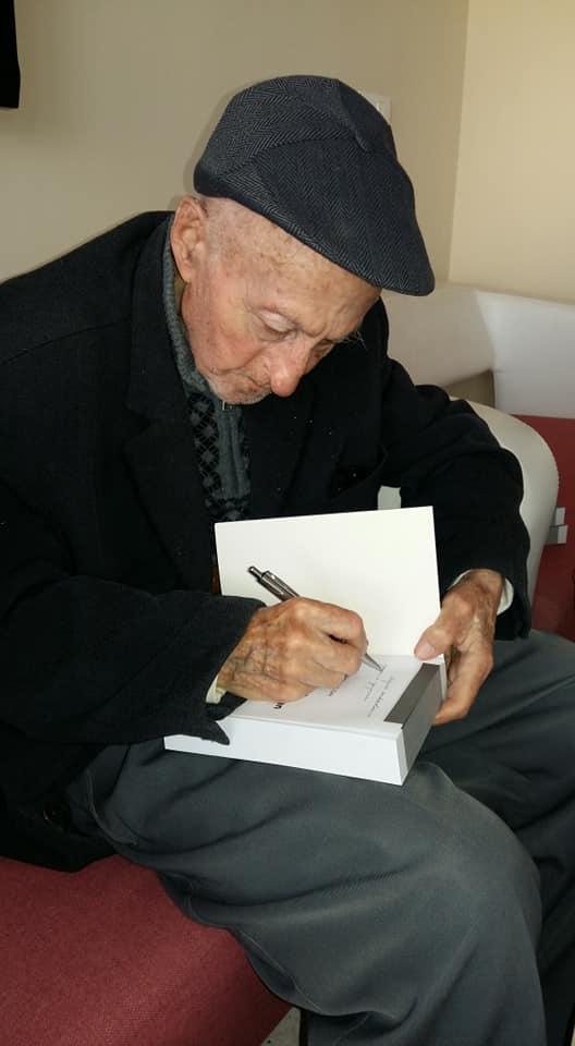 7-Osman Akkuşak kitabını fakire imzalarken